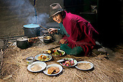 Maria Ermelinda Ayme Sichigalo, a farmer and mother of eight with her typical day's worth of food in her adobe kitchen house in Tingo village, central Andes, Ecuador. (From the book What I Eat: Around the World in 80 Diets.) The caloric value of her typical day's worth of food in the month of September was 3800 kcals. She is 37 years of age; 5 feet, 3 inches tall; and 119 pounds. With no tables or chairs, Ermelinda cooks all the family's meals while kneeling over the hearth on the earthen floor, tending an open fire of sticks and straw. Guinea pigs that skitter about looking for scraps or spilled grain will eventually end up on the fire themselves when the family eats them for a holiday treat. Because there is no chimney, the beams and thatch roof are blackened by smoke. Unvented smoke from cooking fires accounts for a high level of respiratory disease and, in one study in rural Ecuador, was accountable for half of infant mortality.  MODEL RELEASED.