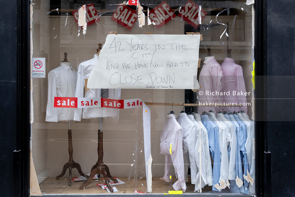 As the UK government tells the nation to prepare for the worst two weeks of the Coronavirus pandemic, a warning aimed at the population to stay at home and minimise contact with others, but in the week when new vaccination centres are opening, is a small menswear shop now forced to close after 42 years in business on Moorgate in the capital's financial district, on 11th January 2021, in the City of London, England.