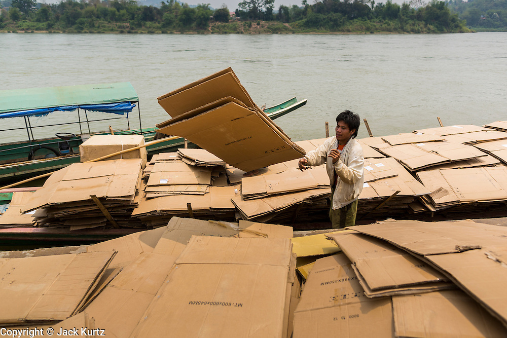 23 APRIL 2014 - CHIANG KHONG, CHIANG RAI, THAILAND: A man recycles cardboard in Chiang Khong port, Thailand. Laos is in the background on the other side of the Mekong River. Chiang Rai province in northern Thailand is facing a drought this year. The 2014 drought has been brought on by lower than normal dry season rains. At the same time, closing dams in Yunnan province of China has caused the level of the Mekong River to drop suddenly exposing rocks and sandbars in the normally navigable Mekong River. Changes in the Mekong's levels means commercial shipping can't progress past Chiang Saen. Dozens of ships are tied up in the port area along the city's waterfront.              PHOTO BY JACK KURTZ