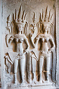 Intricate carving reliefs of Apsara dancers at Angkor Wat. Note that the dancer on the left is pushing her tongue out. In addition to this she has 6 levels to the points of her head-dress. Showing her superiority to the other dancer. This jewel in the crown of Angkor's ancient temples is a vision of beauty, might and Khmer architectural excellence. The five towers dominate the view, which you are led to trough outer walls, along causeways over the moat and past the two giant pools which act as a mirror of the vision. Consecrated at around 1150 to the Hindu god, Vishnu it is suggested that construction took 30 years.