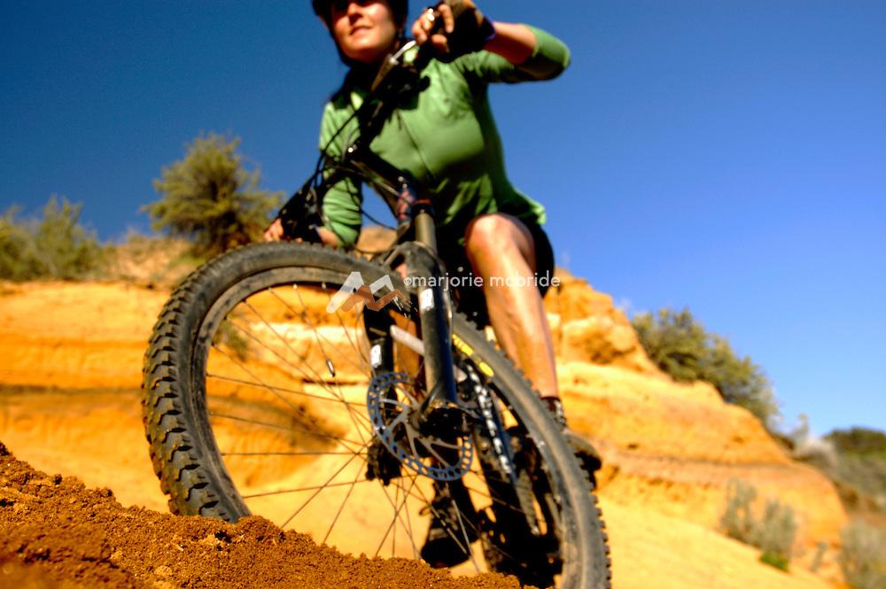 Idaho, Boise.  Woman mountain biking through sandy soil near red rocks on Hull's Gulch trail in the Boise foothills.