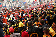 Teams are grouping in the City Square for the closing day of the Battle of the Oranges and to celebrate the historical victory of the people against their oppressor, in Ivrea, pop. 30.000. During the days of the Carnival, the town becomes crammed with tourists coming to witness the event which finds its roots at the end of the XII Century, when the people led an insurrection against the local tyrant, Count Ranieri of Biandrate, who was exercising the 'jus primae noctis' rule (having the first night) on the local young brides. The battle to overthrow him is represented with a 3-day-fight between factions in which more then 400 tonnes of oranges are thrown. During the celebrations, food stalls, bands playing music, and parades are also present, giving it a typical Medieval atmosphere. .
