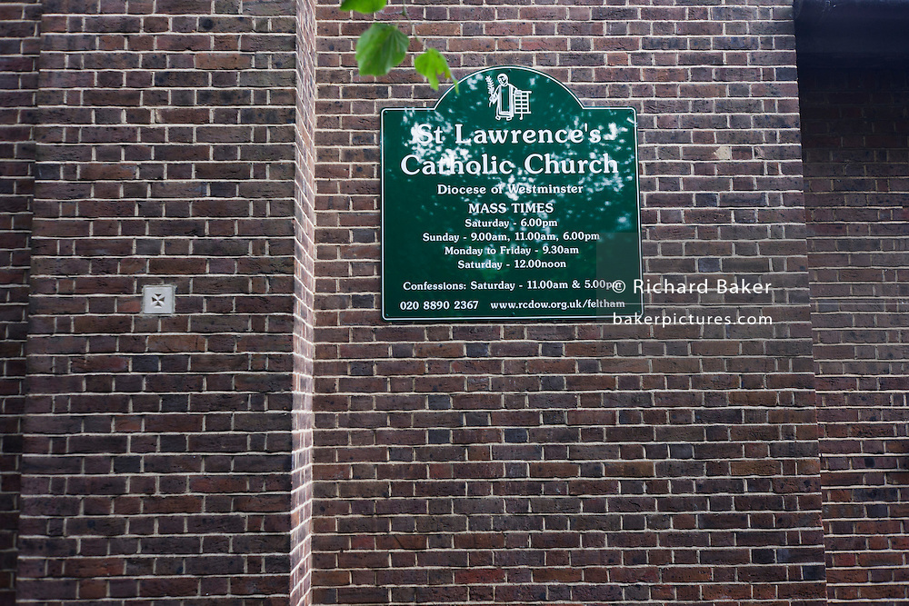 Exterior name, mass times and contact sign for St. Lawrence's Catholic church in Feltham, London.