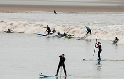 © Licensed to London News Pictures.  22/03/2015. Gloucestershire, UK.  Surfers ride the Severn Bore at Newnham and Minsterworth.  The alignment of the sun and moon creates high tides going up the river Severn this weekend for the biggest Bores of the year.  Photo credit : Simon Chapman/LNP