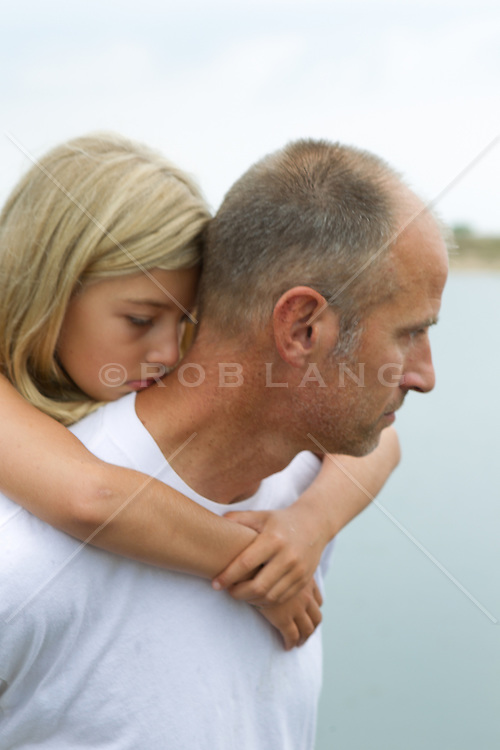 little girl holding on to her father's back for a piggy back ride