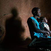 Liliosa, 16, carries her baby at home in Masvingo Province, Zimbabwe. She forages for food in the wild for her, her baby and her young sister, who is born HIV positive. <br /> <br /> Drought in southern Africa is devastating communities in Zimbabwe, leaving 4 million people urgently in need of food aid. The government declared a state of emergency,. <br /> <br /> Here in Masvingo Province, the country's hardest hit province, vegetation has wilted, livestock is dying, and people are at serious risk of famine. <br /> <br /> Pictures shot by Justin Jin