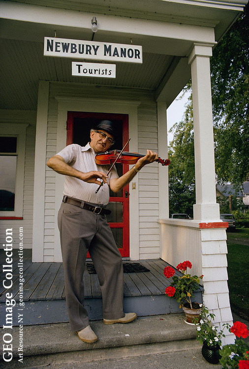 Fiddler poses with his violin on porch of a guest house during annual contest for musicians at Cracker Barrel Bazaar Fiddlers Contest.