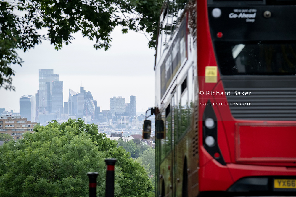 With the skyscrapers of the City of London, the capital's financial district, in the distance, a London bus turns down Sydenham Hill, on 15th June 2021, in south London, England.