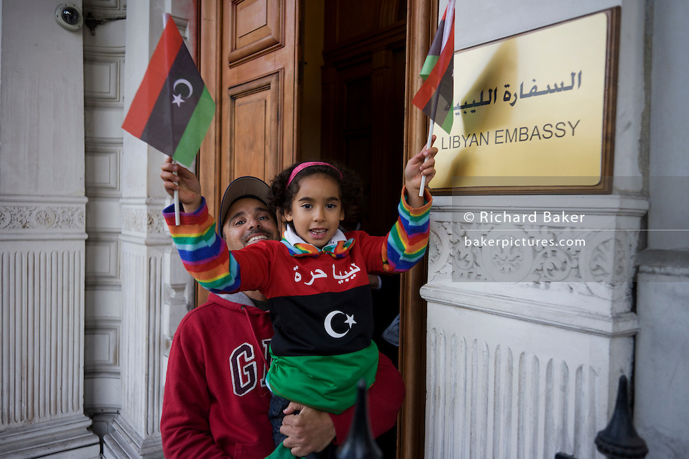 Reacting to the death earlier in Sirte of the dictator Muammar al-Gaddafi, a young Libyan child whose grandfather was killed by the Gaddafi regime in 1979, celebrates by waving the revolutionary flag with her father outside their London embassy in Knightbridge, central London.