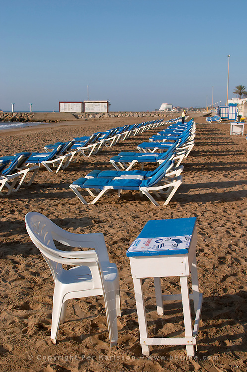 The beach. Rows of empty deck chairs. A plastic chair and parasol for the cashier attendant. Sitges, Catalonia, Spain