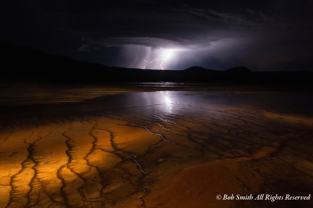 A lightning storm approaches from the west side of Yellowstone National Park while light painting the bacteria beds at Grand Prismatic Spring.