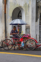Penang Rickshaw - Taking a trishaw ride through Penang seems to be the thing to do for every visitor.  There are dozens of them offering this service and the price is fixed these days at 40 Malaysian Ringgit per hour. Unlike other towns where rickshaws still ply the streets, the fixed rate ensures a reasonable fare for passengers and an equitable income for the driver. The trishaws in Penang are colorful with lots of decorations, each with their own individual design and add flambouyant colors to the streets of Penang.