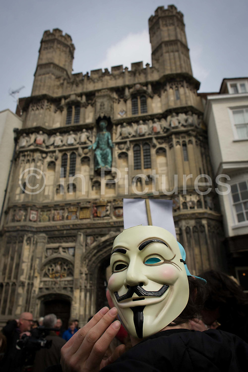 An anonymous protester demonstrates against the Tory coalition below Church Gate in Butter Market. Against public service cuts during the enthronement for the new Archbishop of Canterbury, Justin Welby. Their protest is about coalition plans over the NHS, urging the government to keep the country's National Health Service out of private hands, to keep it as a government organisation, run by Jeremy Hunt and overseen by his boss, Cameron. The town of Canterbury hosted the enthronement of the Church of England's new Archbishop, allowing Medway locals to voice their concerns.