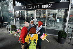 © Licensed to London News Pictures. 16/03/2019. LONDON, UK. People taking part in a Stand Up To Racism and Stand Up To Islamophobia march through the capital pay respects by next to floral tributes outside the New Zealand High Commission on Haymarket following the recent attack in Christchurch, New Zealand, where 49 people were killed.    Photo credit: Stephen Chung/LNP