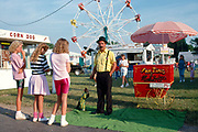 Three teenage girls looking at a monkey at the county fair in Meredosia, Illinois