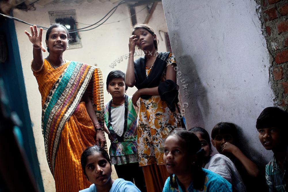 Anita Suresh Kasbe, 41, (left) the Unicef community facilitator is teaching to the girls - and others - attending the Unicef-run 'Deepshikha Prerika' project inside the Milind Nagar Pipeline Area, an urban slum on the outskirts of Mumbai, Maharashtra, India.