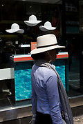 Woman walks past a sunglasses shop featuring three hats suspended from the store window ceiling. The lady consumer passes the dark window selling summer eyewear in London's Long Acre, a street near the capital's Covent Garden, Westminster. Walking along the street, the woman wears a similar wide-brimmed hat to the three white hats that symbolise a London summer, hanging in clear space above the woman's head.