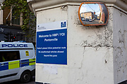 """A """"Welcome to HMP/ YOI Pentonville"""" sign displayed on the iconic entrance pillars around the external perimeter of HM Prison Pentonville, London, United Kingdom.  The traffic safety mirror is broken, but shows the reflection of cars parked on the prison grounds. Pentonville is a local prison and holds Category B and C males and A Wing is for this who are on remand and convicted. The prison was built in 1816 as a modern prison and was uniquely designed for rehabilitation.  A Metropolitan Police van passes the entrance on the street while on patrol. (Photo by Andy Aitchison)"""