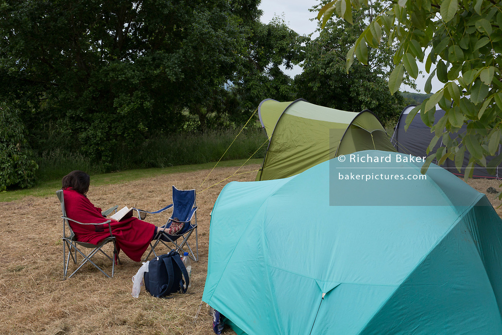A lady reads her book next her small tent early in the morning after a 50th birthday party in the Herefordshire countryside, on 23rd June 2019, in Kington, Herefordshire, England.