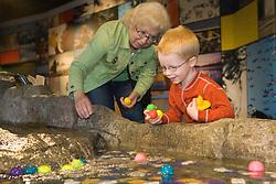United States, Washington, Bellevue, KidsQuest Children's Museum, grandmother and boy playing at Waterways exhibit