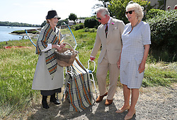 The Prince of Wales and Duchess of Cornwall (right) are shown traditional oyster fishing methods during a visit to Llangwm, in west Wales.