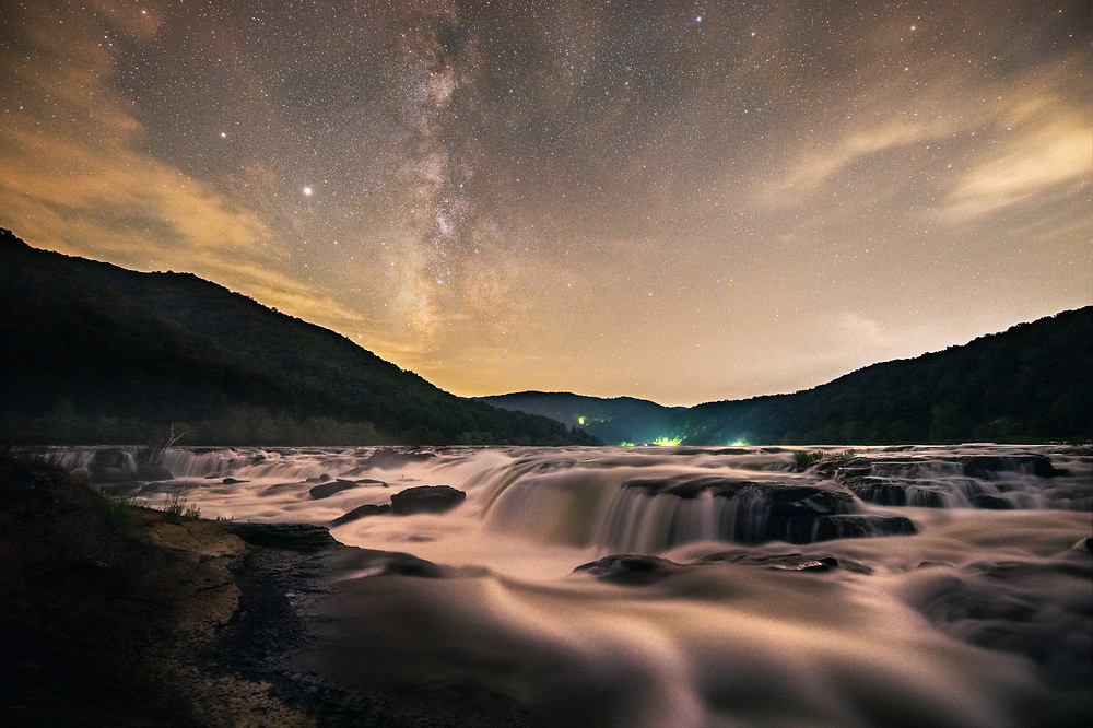 A late summer Milky Way streams above a flowing Sandstone Falls of the New River in West Virginia, appearing to luminesce under the starry night sky.