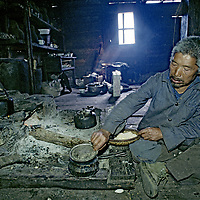 CHINA, TIBET.  Menba villager eats lunch of roasted barley flour (tsampa) by home hearth in remote Payi, near mouth of Tsangpo River Gorge in eastern Himalaya.