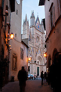 Street scene with the Duomo di Orvieto rising at the end of the corridor, Umbria, Italy.