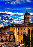 """""""The New Church Bell Tower, home of St. Francis of Assisi""""…<br /> <br /> After a progressive but slow assent up to the mountaintop of Assisi, I took time to pause, look over my shoulder, and truly appreciate all I had seen. God always seemed to illuminate my forward path; however, He also left a glow of remembrance from where the journey began. This evening view is from the Basilica di Santa Chiara (Basilica of St. Clare), a 13th-century church that houses the relics of St. Clare, friend and protégé of St. Francis of Assisi, and the 12th-century crucifix that spoke to St. Francis at San Damiano. This image is a rear view of the church and campanile of The Chiesa Nuova, built in 1615 on the site of the birthplace of St. Francis. The church was aptly named Chiesa Nuova because it was the last church to be built in Assisi at that time. The """"New Church"""" can be defined not so much as the Shrine of St. Francis, but the Sanctuary of St. Francis where he developed his roots of holiness."""