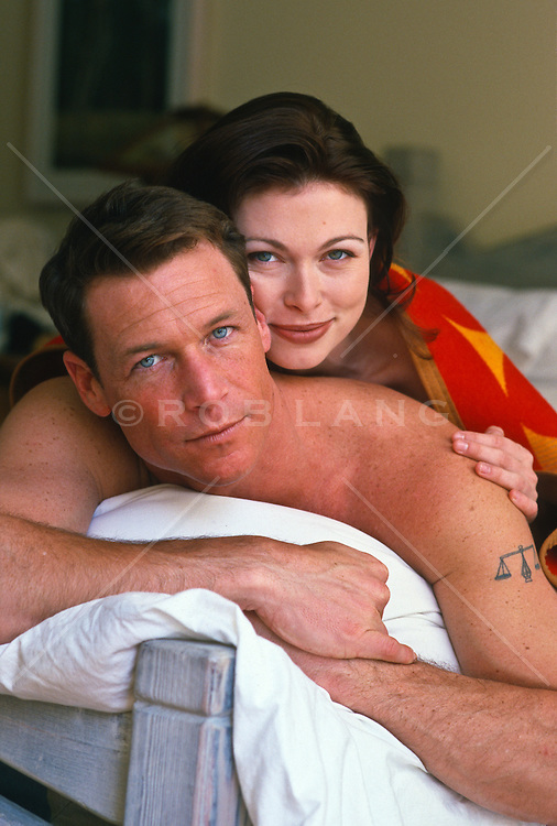 couple on a bed looking at camera