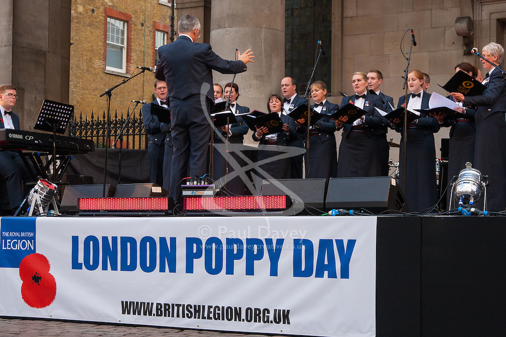 Covent Garden, London, October 30th 2014. They Royal British Legion's Poppy Day in London centred around Covent Garden where bands, choirs, classical and pop musicians entertained crowds as Air Force personnel carrying donation buckets sold poppies, hoping to raise in excess of £1 million. Pictured: Tenor Jonathan Antoine entertains the crowd in Covent Garden. A choir from the Royal Air Force performs in Covent Garden.