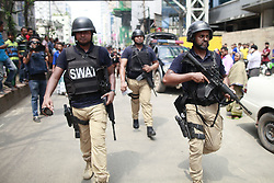 August 15, 2017 - Dhaka, Bangladesh - SWAT (Special Weapons And Tactics) team of Bangladesh police leave the shooting scene after they tried to flush out suspected Islamist radicals who have holed up in a building in Dhaka, Bangladesh. A suspected militant was killed in a suicide blast during a raid on a hotel in Dhaka on Tuesday. Islamist Militant Saiful Islam blew himself up during the raid despite repeated requests to surrender. The law enforcement agencies cordoned off Hotel Olio International. A portion of the hotel's fourth story reportedly collapsed and fell onto the road after the explosion causing injuries. (Credit Image: © Suvra Kanti Das via ZUMA Wire)