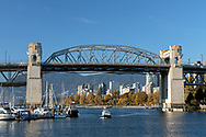 The Burrard Street Bridge (completed in 1932)  and Vancouver's False Creek. Sunset Beach and apartment towers in the West End of Vancouver are in the background.  The small boat in the creek is one of the False Creek Ferries that crosses False Creek from near Sunset Beach to Granville Island.  Photographed from Granville Island in Vancouver, British Columbia, Canada.