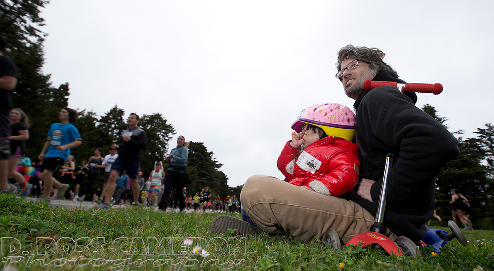 San Franciscan Michael McManus, right, takes in the passing show with daughters Zola and Juliet, both 3, during the 104th running of the Bay to Breakers 12k, Sunday, May 17, 2015 in San Francisco. Tens of thousands of runners, some clad in costume and some in nothing at all, populated the 7.42-mile route. (D. Ross Cameron/Bay Area News Group)