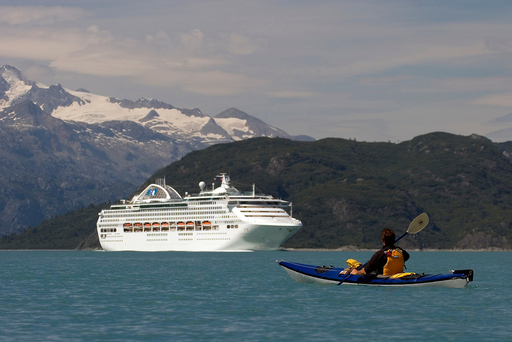 A kayaker and cruise ship share Glacier Bay National Park waters.