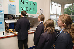 Secondary school students queuing up for lunch at school canteen,