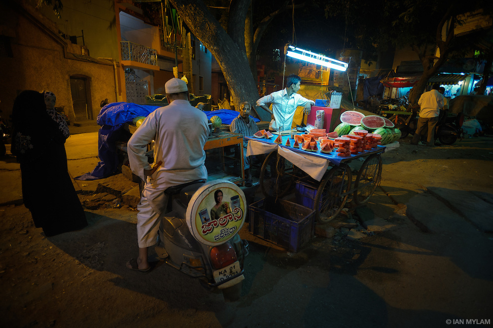 A street vendor sells melons from a cart in Bangalore, India.