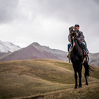 9 year old Aibek on his horse in Kyrgyzstan. Like other semi-nomadic herders in Kyrgyzstan, Aibek lives with his family in a yurt camp during the summer months when their grazing animals are moved to higher pastures. At the end of summer they decamp back to their town and Aibek returns to school.