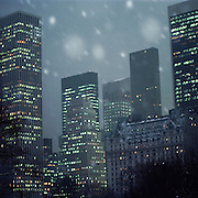 Central Park South and 5th Avenue skyscrapers, office towers and hotels in nighttime snow storm.