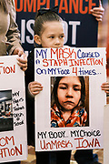"11 JANUARY 2021 - DES MOINES, IOWA: A child holds up a sign in the Rotunda of the Iowa State Capitol in Des Moines. Hundreds of Iowans from across the state came to the State Capitol to protest the Governor's COVID-19 mitigation efforts. The Coronavirus (SARS-CoV-2) mitigation guidelines include a mask mandate indoors when it isn't possible to social distance. But the Governor specifically exempted the State Capitol. No one in the crowd wore a mask and there was no effort to follow ""social distancing"" guidelines. There were also ""anti-Vaxxers"" in the crowd who protested the vaccine efforts and said vaccines were unsafe.           PHOTO BY JACK KURTZ"