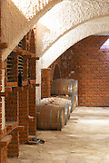 Wine cellar with bottle bins and oak barrels, arched vaulted ceiling. Matusko Winery. Potmje village, Dingac wine region, Peljesac peninsula. Matusko Winery. Dingac village and region. Peljesac peninsula. Dalmatian Coast, Croatia, Europe.