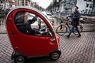 Nederland, Amsterdam,  2 maart 2014<br /> Nieuw type invalidenwagentje. Heel smal karretje met een leuk ontwerp. Er kan maar 1 persoon in zitten, het ding is niet veel breder dan een fiets en kan daarom ook makkelijk op het trottoir geparkeerd worden. <br /> Foto(c): Michiel Wijnbergh