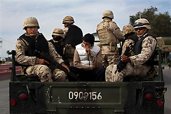 Members of the Mexican army escort a suspect they found carrying drugs on a bus in Ciudad Juarez.