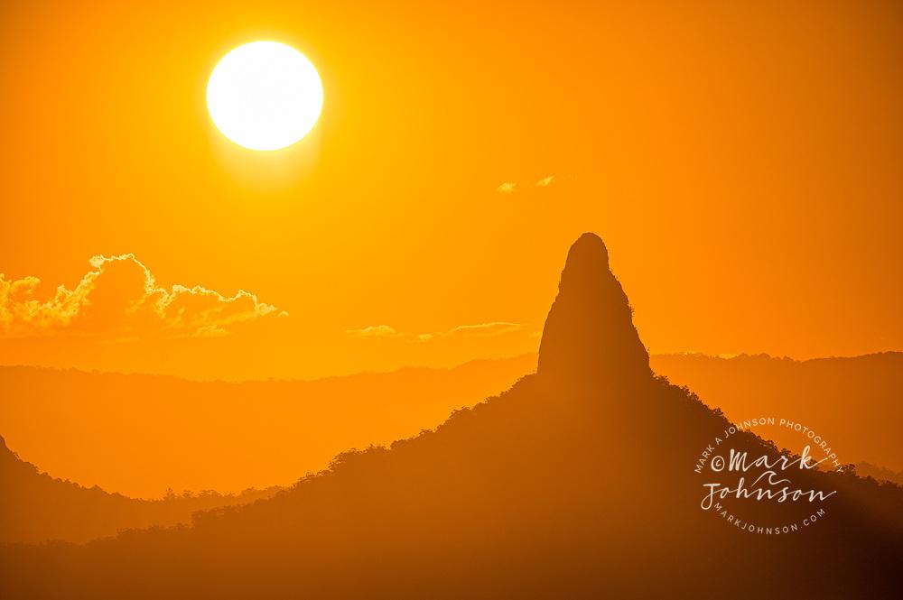 The sun setting behind Mt Coonowrin, Glass House Mountains, Sunshine Coast, Queensland, Australia