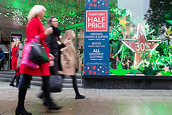"""© Licensed to London News Pictures. 24/11/2015. London, UK. Shoppers walk past a """"Today Only Half Price"""" sign displayed in the shop window of Debenhams on Oxford Street. Photo credit : Vickie Flores/LNP"""