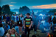 Revellers at the stone circle overlooking Glastonbury.<br /> Glastonbury Festival is the largest greenfield festival in the world, and is now attended by around 175,000 people. It's a five-day music festival that takes place near Pilton, Somerset, England. In addition to contemporary music, the festival hosts dance, comedy, theatre, circus, cabaret, and other arts. It is organised by Michael Eavis on his own land, Worthy Farm in Pilton. Leading pop and rock artists have headlined, alongside thousands of others appearing on smaller stages and performance areas.