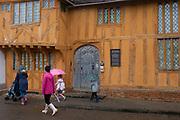 Schoolchildren and mothers walk in the rain past the medieval Little Hall  in Lavenham, on 9th July 2020, in wool town Lavenham, Suffolk, England. Little Hall is a late 14th Century hall house on the main square, its story mirrors the history of Lavenham over the centuries. First built in the 1390s as a family house and workplace, it was enlarged, improved and modernised in the mid 1550s, and greatly extended later. By the 1700s it was giving homes to six families and was restored in the 1920s/30s. The wool trade was already present by the 13th century, steadily expanding as demand grew. By the 1470s Suffolk produced more cloth than any other county.
