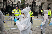 Extinction Rebellion 'crime scene investigators' in white suits and masks walking past Downing Street to investigate areas of ecocide in a performance on 7th September 2020 in London, United Kingdom. The 20 investigators were protesting at the Brazilian government's alleged involvement in ecocide in the Amazon, and the UK government's ecocide along the HS2 route. Extinction Rebellion is a climate change group started in 2018 and has gained a huge following of people committed to peaceful protests. These protests are highlighting that the government is not doing enough to avoid catastrophic climate change and to demand the government take radical action to save the planet.
