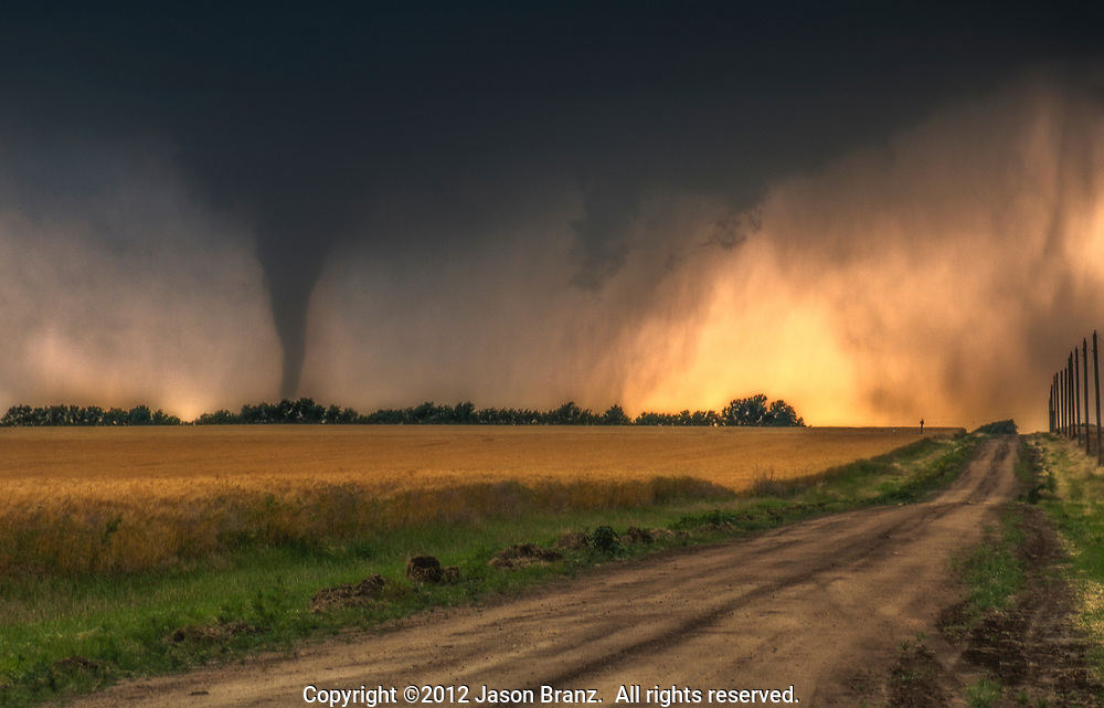 Tornado looming over a dirt road and wheat field, southern Kansas.
