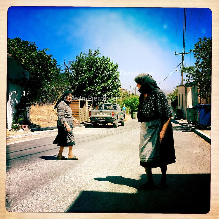 Kreta, Kroustas , 23 juli 2013.<br /> <br /> Bewoonsters van bergdorpje Kroustas even ten Zuiden van Kritsa in het Noord Oosten van Kreta.<br /> Summer holiday on the Greek island of Crete. Two women greeting each other. Streetview